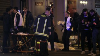 Rescue workers and medics work by victims in a Paris restaurant, Friday, Nov. 13, 2015. Police officials in France on Friday reported a shootout in a Paris restaurant and an explosion in a bar near a Paris stadium. It was unclear if the events were linked. (AP Photo/Thibault Camus)