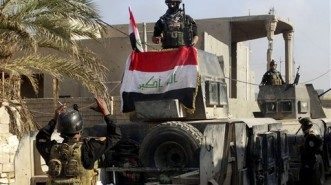 Iraqi security forces surround the government complex in central Ramadi, 70 miles (115 kilometers) west of Baghdad, Iraq, Monday, Dec. 28, 2015. Iraqi military forces on Monday retook a strategic government complex in the city of Ramadi from Islamic State militants who have occupied the city since May. (AP Photo/Osama Sami)