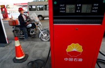 A Chinese man waits to fuel up his motorbike at a petrol station in Suining, southwest China's Sichuan province on March 27, 2012.  Sinopec and its parent China Petrochemical Corp. are ramping up domestic and overseas oil and gas production to counter losses from selling diesel and gasoline at state- mandated prices.  CHINA OUT AFP PHOTO (Photo credit should read STR/AFP/Getty Images)